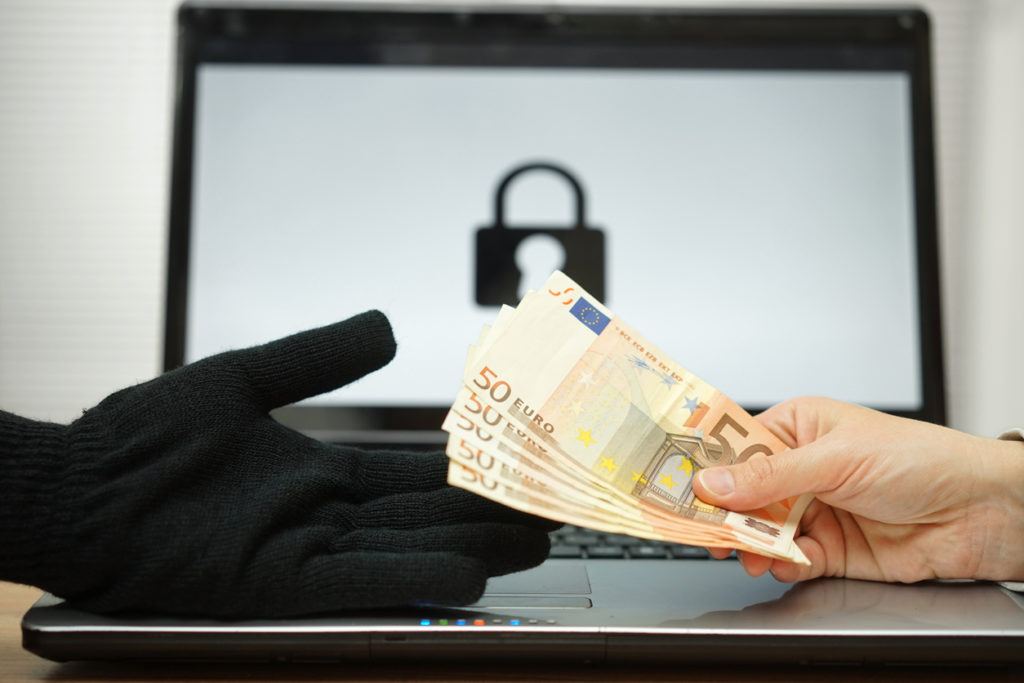 An image of a computer locked by ransomware and a user paying a cyber criminal to get access to their computer and files again.