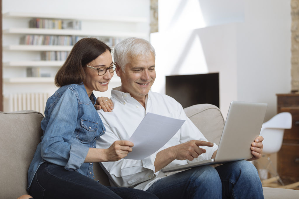 Mature couple working on a computer while reading instructions.