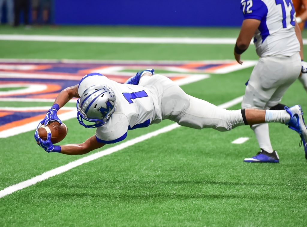 Football player diving into the end zone.