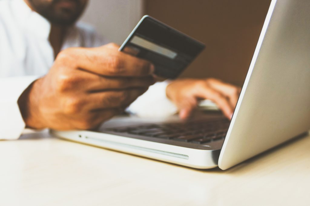 Image of someone at his computer using credit card for donating online.
