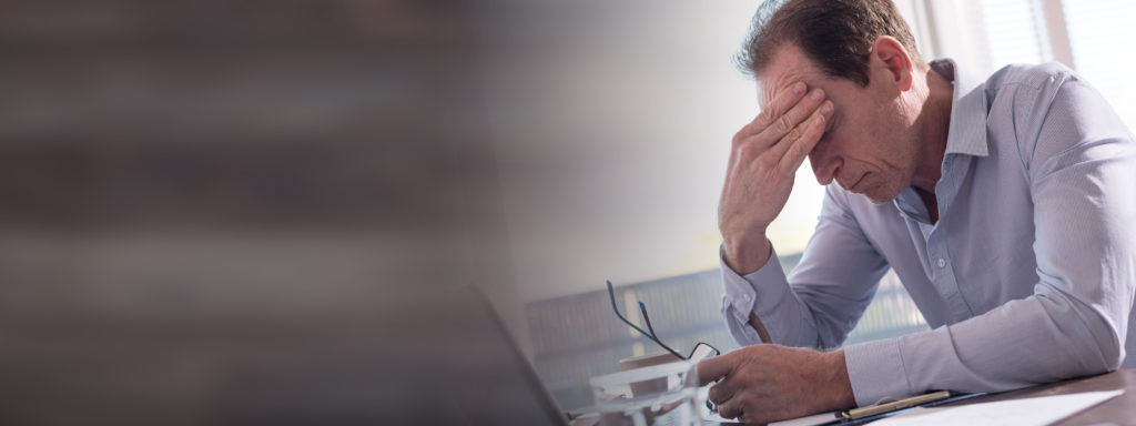 Stressed businessman sitting in office with hand on forehead