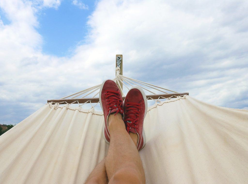 An image of someone relaxing on a hammock. Make sure your vacation is relaxing by avoiding these common vacation scams.
