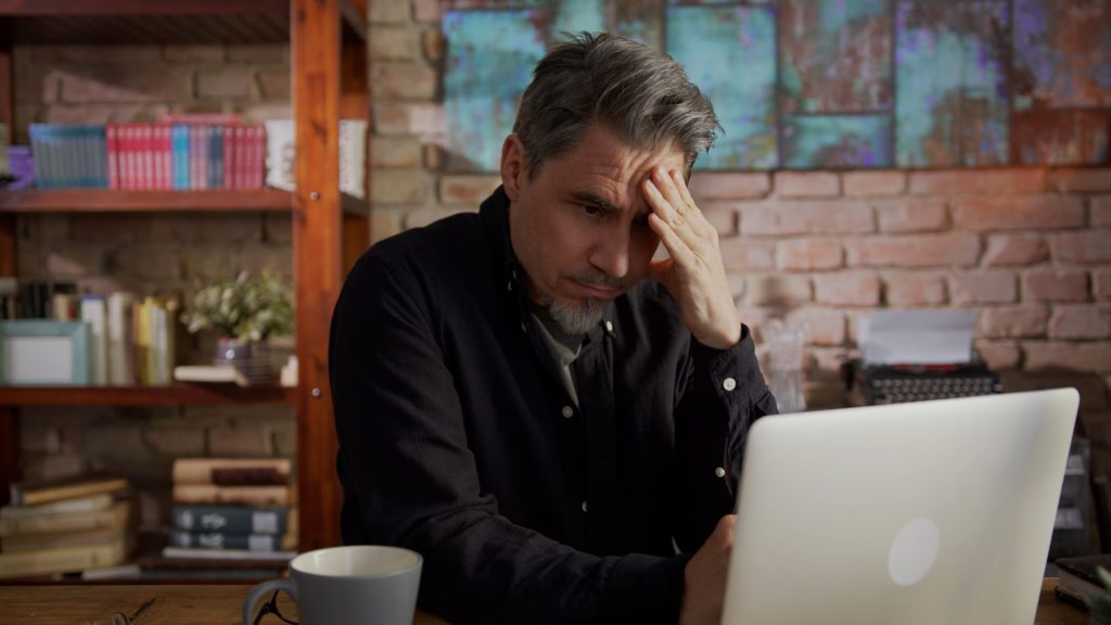 An image of a man looking worried at his computer because he has ransomware.