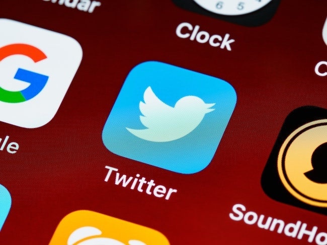 An image of the Twitter app logo on a phone.