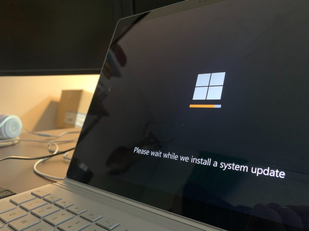An image of a Windows update loading on a laptop.