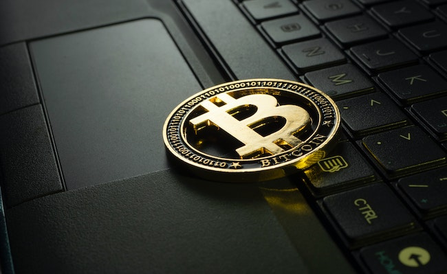 """An image of a """"B"""" for bitcoin, sitting on a laptop computer. Bitcoin is a type of cryptocurrency, a form of digital currency where information about transactions is stored on a database."""